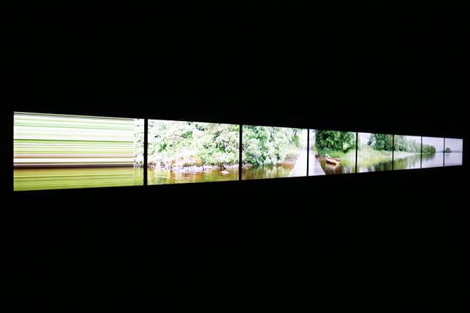 高谷史郎氏/「Toposcan / Ireland 2013」―16:9のモニター8台が、全体でひとつの映像となるように横一列に連結。横長の映像の中をモニター1画面分の映像が、横切るようにゆっくりと端から端へ移動