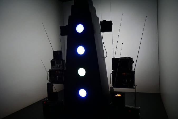 和田永氏/「蟹足電輪塔」-蟹の足を模した塔に収められたブラウン管モニターがさまざまな縞模様を映し出す。その周りに置かれたラジオからは、映像のパターンと同期して、さまざまな音色の音が出力される