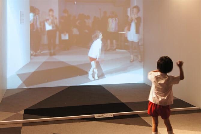 「Dancing Mirror / 松村誠一郎」スクリーンの前で動くと、少し前の動きを記録して音楽に合わせて早送り・巻き戻しで再生する。何気ない動作や仕草がダンスのような動きに変化する
