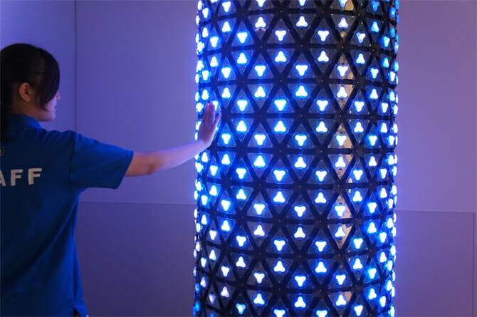 「センスピラー / 森脇裕之」円筒形の作品に手をかざすとセンサーが反応し、触れた部分から順に連鎖して光っていく
