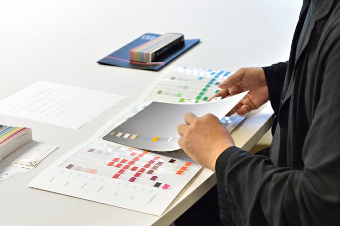原氏が手にしているのは、白から黒のグラデーションとデザインパターンが印刷された背景色の選定用シート。カラーチップの下に挿し込むことで彩度やコントラストのバランスなどを確認できる。色自体は同じでも背景が異なると見え方は大きく異なってくることを配慮した設計だ