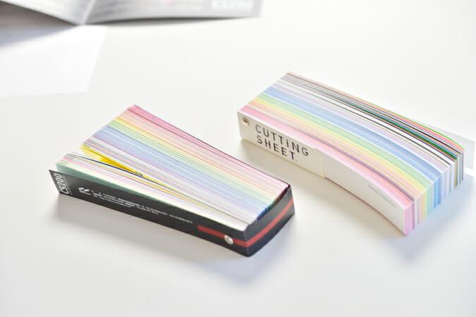 厚手の紙製のホルダーのおかげで、カラーサンプルをきれいに束ねられるハンディな短冊型の見本帳(右)