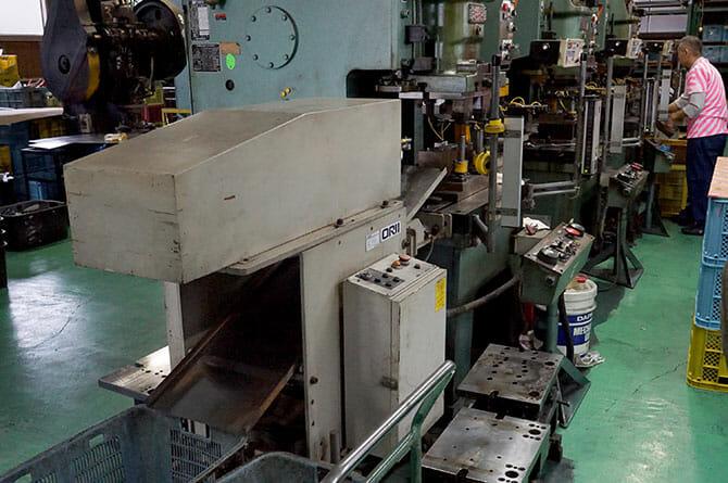 三つの機械を組み合わせたライン、平らな鉄板がシャベルに成形される