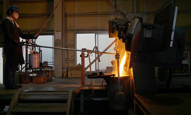 三条特殊鋳工所にて、炉から流れ出る鉄、これを鋳型に流し込む