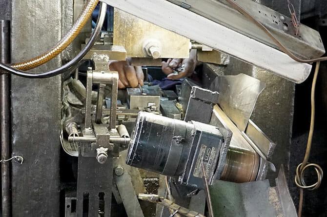 日本洋食器にて、プレス機に材料を置き次々と生み出されるスプーン
