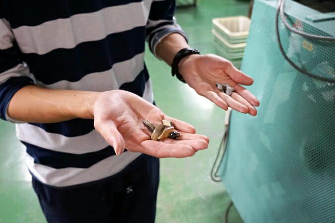 フレームの艶感を生み出す、バレル研磨という手法について研磨チップを手に取り教えていただいた