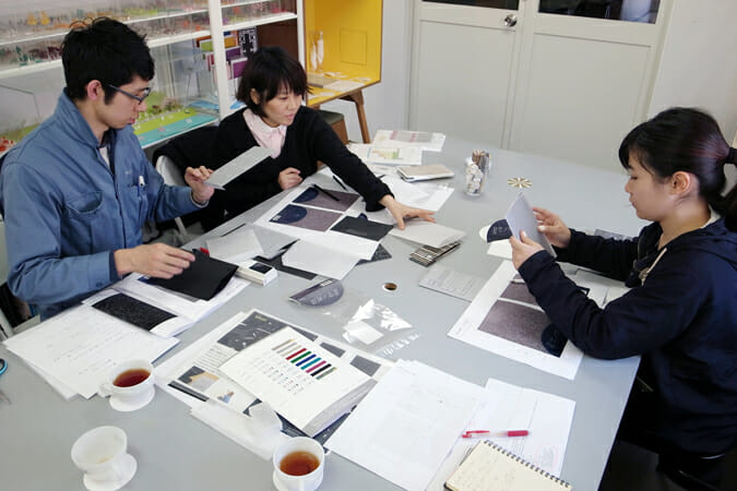 宮田泰地さん(福永紙工)、瀧ひろみさん( switch design)さんと、打ち合わせをする塚田萌さん