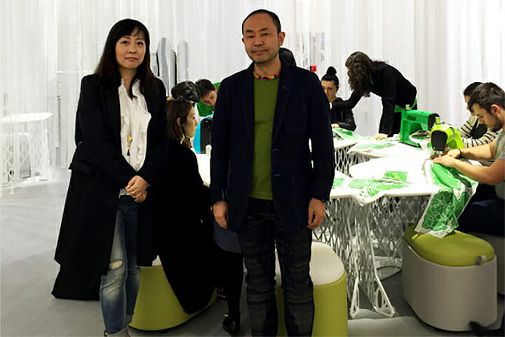 伊藤志信氏(左)伊藤節氏(右)、アイシン精機の家庭用ミシン「OEKAKI50」の体験コーナー用家具TORTAの前で