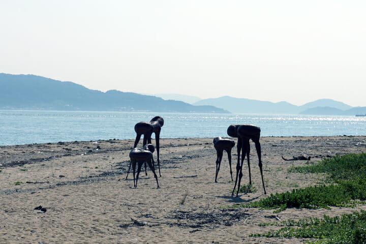 「怪物と少年Ⅱ/この彫刻は一万年の生命を持ちヒトの一生の間には10mほど歩くⅢ」伊東敏光。浜辺に佇む4頭の怪物がはじめは不気味でしたが、だんだん神聖な生き物に見えてきます