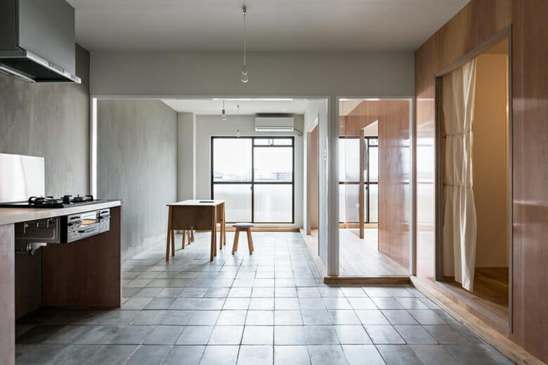 ハイツYの修理 既存の間取りをそのままに、居室を横断するように挿入した木質素材の壁のみで各室の関係性を変化させ、様々な居住形態に対応するものへと更新。挿入した壁の素材であるラワン合板表面に貼られた「IROMIZU」。合板という素材の特性である経年変化を透過しつつ、経過してゆく時間を可視化する。また、貼られたIROMIZUは室内外の風景の映り込みや光の反射を表面上で現象させる