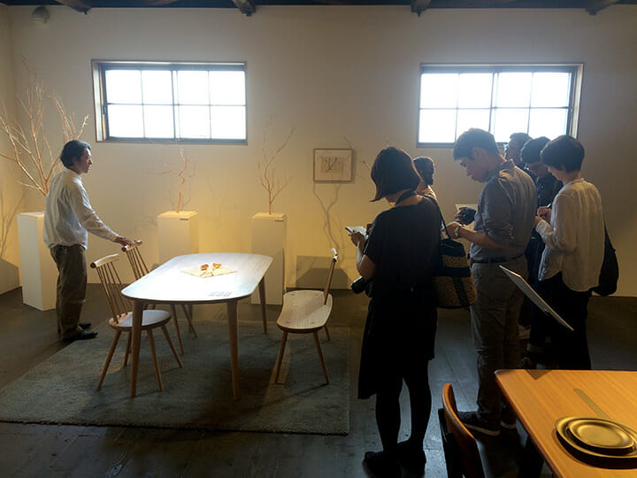 枝の美しさを活かした椅子「kinoe」をジャーナリストに説明するデザイナー貝山伊文紀氏、飛騨産業ショールームにて