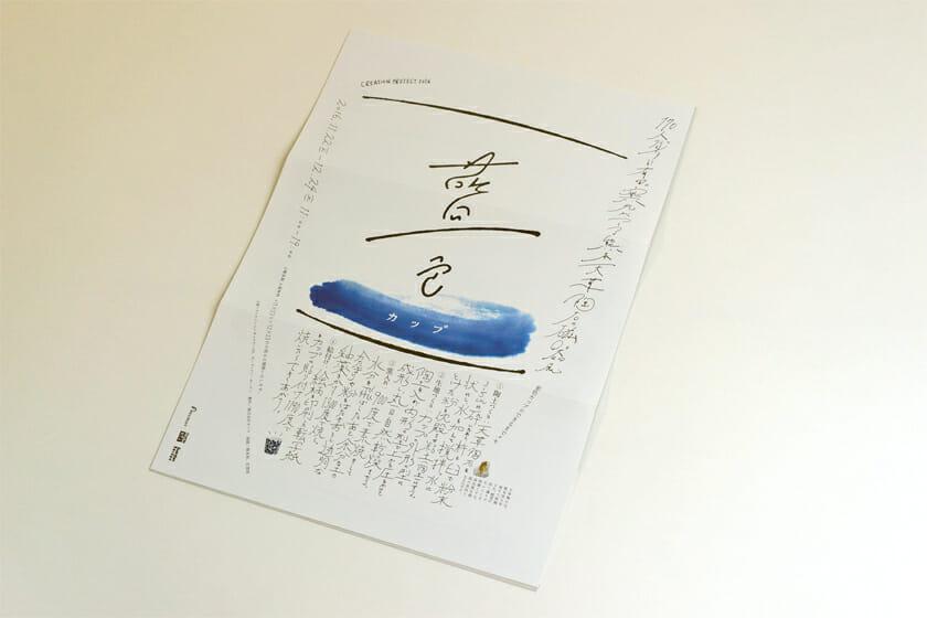 藍色カップ(展覧会フライヤー)。170人のクリエイターと有田の窯元がつくる磁器展のフライヤー。デザインは大原大二郎さんが担当。既成の文字はほとんど使わず、手描きの文字と線で構成された仕上がりはインパクト大!