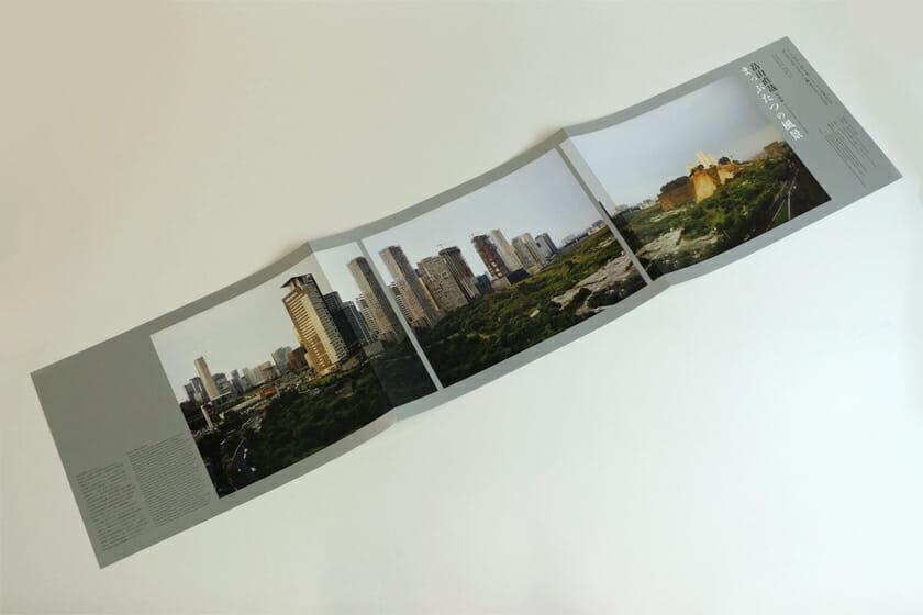 畠山直哉 写真展 まっぷたつの風景(展覧会フライヤー)。横長に三面開きになるフライヤーは、長細い窓から風景を見ているかのよう。光沢のある銀色の紙に印刷された、贅沢な仕上がりです