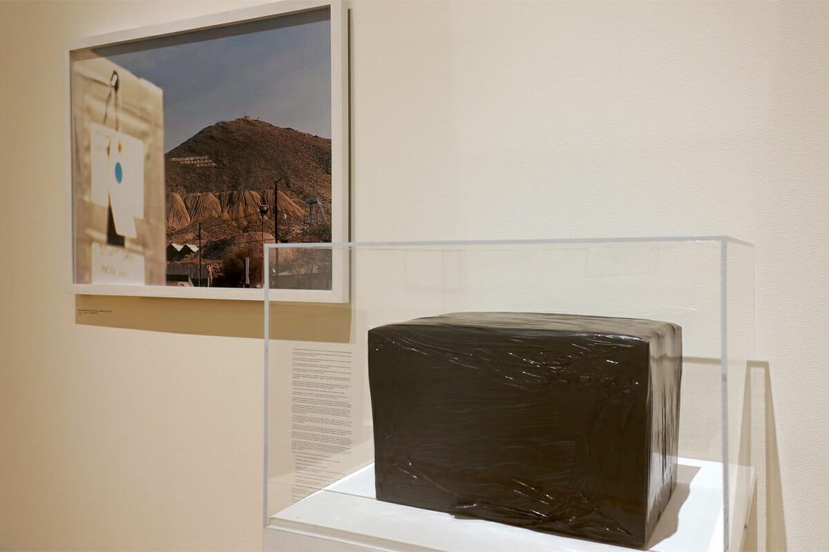 「Memorandum JB CH AG (Brother) – (Alchemy Box No. 10.1) 2008」/ライアン・ガンダー。日本語で「錬金術の箱」というタイトルを持つ作品。箱の中に入っていると書かれているのは、ガラスや道具など日常的なものですが本当に入っているかは不明。また、同じ中身の箱がサンフランシスコ郊外に埋められており、その埋められた場所の写真とセットになっています。そのモノが持つ「価値」は見る人の信じる力にかかっているという作品