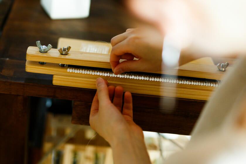 糸で編むことでパーツとパーツの間に糸のクッションができ、滑らかに動く。穴に通すとガラス同士がくっついてしまうので、ガチャガチャ音がしてしまうという