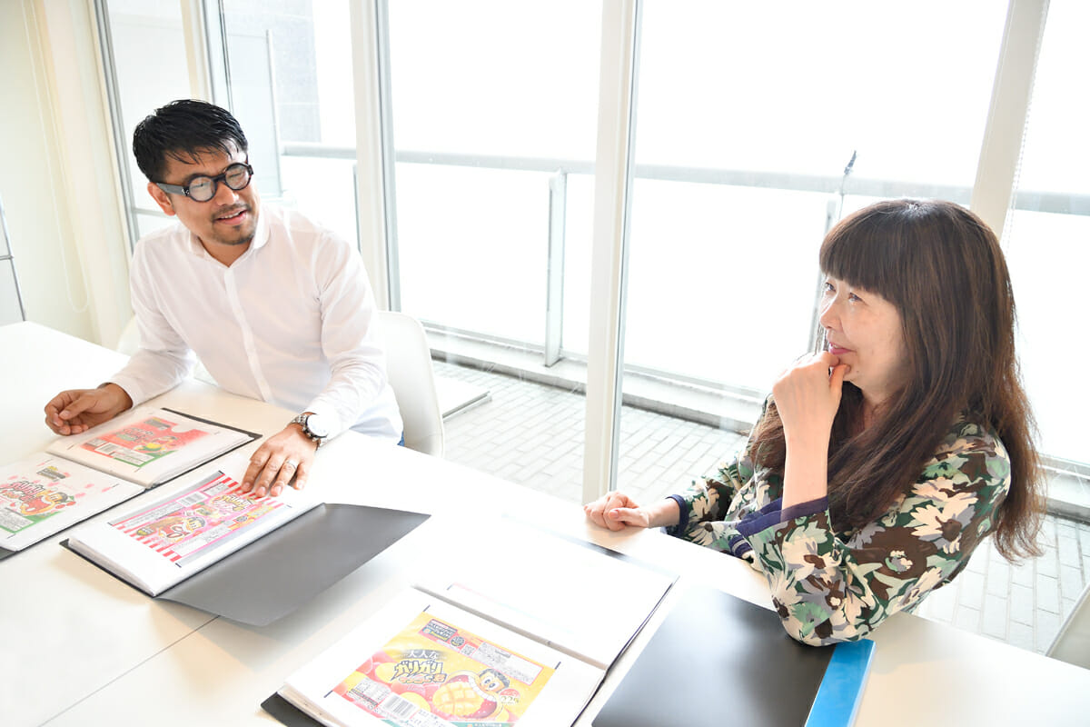 (左)高橋俊之:桑沢デザイン研究所グラフィック研究科を卒業し、1997年有限会社Gを設立。2006年赤城乳業と共同出資で有限会社ガリガリ君プロダクションを設立。1999年以来「ガリガリ君」のパッケージデザインやCM、ポップ、イベント、ライセンス商品のパッケージ、販促物にいたるまですべて手がける。(右)楠原美夏:成城大学経済学部卒業後、デザイン制作会社ライトパブリシティ勤務。その後渡仏し、帰国後はハヤサキスタジオ(写真スタジオ)に勤務。多摩美術大学デジタルデザイン入学。中退後、1997年に有限会社Gを設立