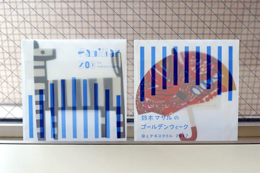 """鈴木マサルのゴールデンウィーク 傘とテキスタイル 2017(展覧会DM)。テキスタイルデザイナー・鈴木マサルさんが、多くの人にテキスタイルデザインを身近に感じてほしいという思いから、""""傘""""という定型のアイテムにテキスタイルデザインをのせて、""""持ち歩くテキスタイル""""という企画ではじめた展覧会。6年目の開催となる今回の会場とDMのデザインは、デザインチーム「minna(ミンナ)」が手がけました。"""