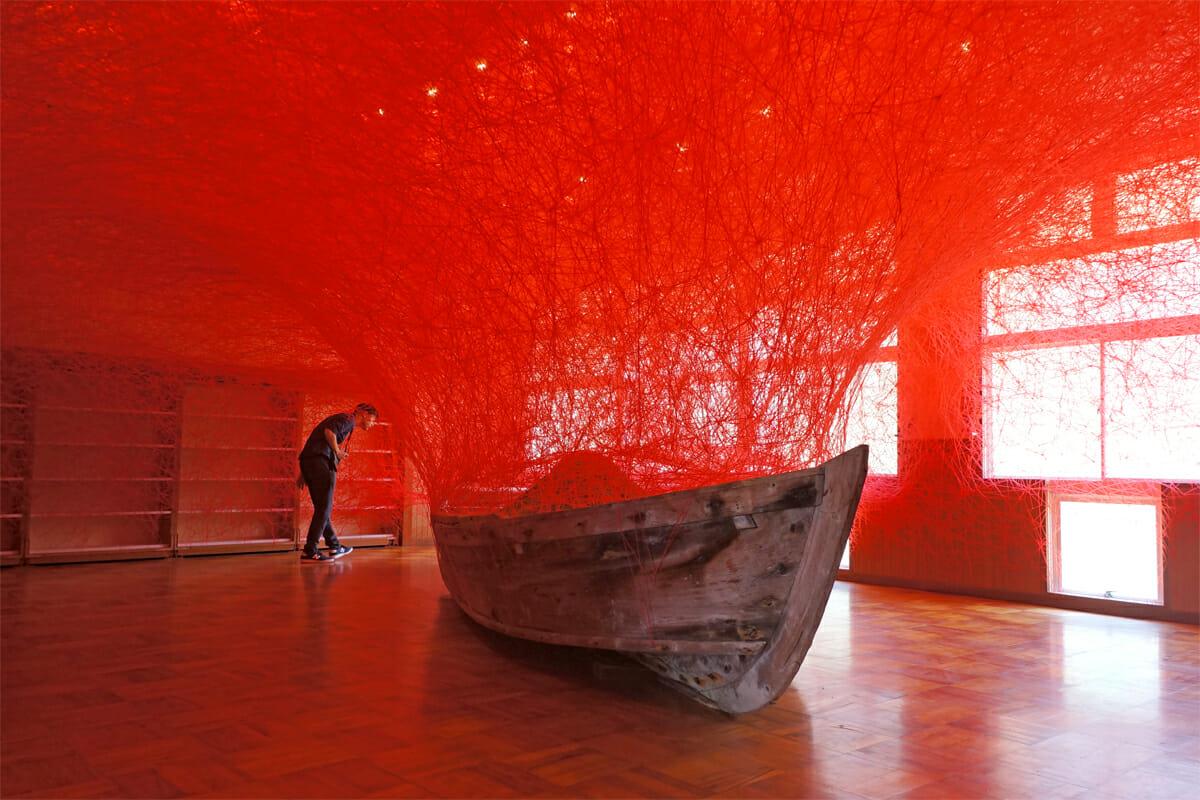 時を運ぶ船(塩田千春)。実際に使用されていた砂取船に砂を乗せ、その船の周りを真っ赤な糸で編みこんでいます。使用した糸の数は、なんと1,000玉(約8,000m)!