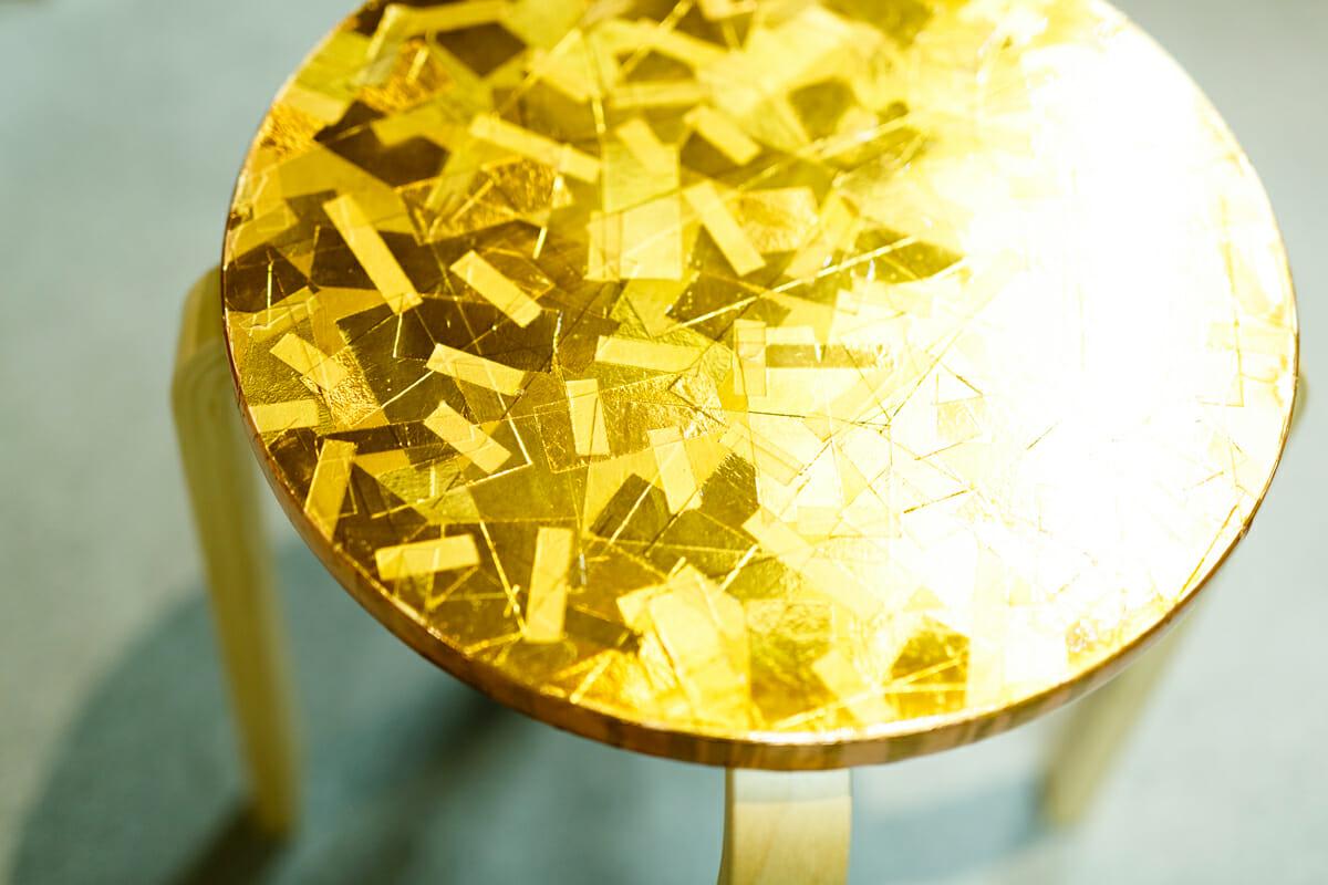 西尾さんが座面を銅のテープで加工したイス。もとは銅本来のピンクっぽい色だったものが、経年変化で黄色く変わっていったそう