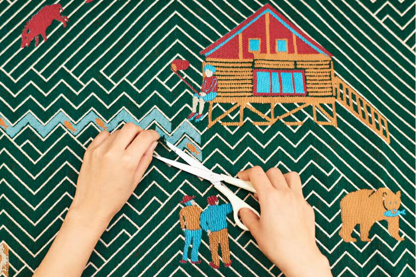 表層の糸が浮いている部分にハサミを入れることができるようになっており、カットしていくと下から図柄が出てきて新たなストーリーを加えることができる。写真は西粟倉の山からインスピレーションを受けて製作された「SATOYAMA」。