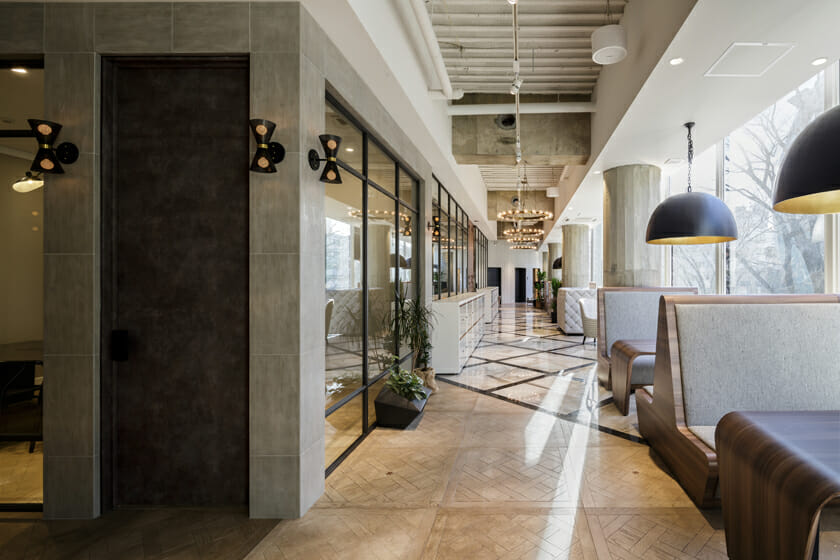 <2階写真>表参道に面したビルの2~3階を使ったオフィス。無機質なコンクリート、木材、クラシカルなタイルといった質感の違う素材を組み合わせ、ジャンルにとらわれない自由な会社であることを表現した。