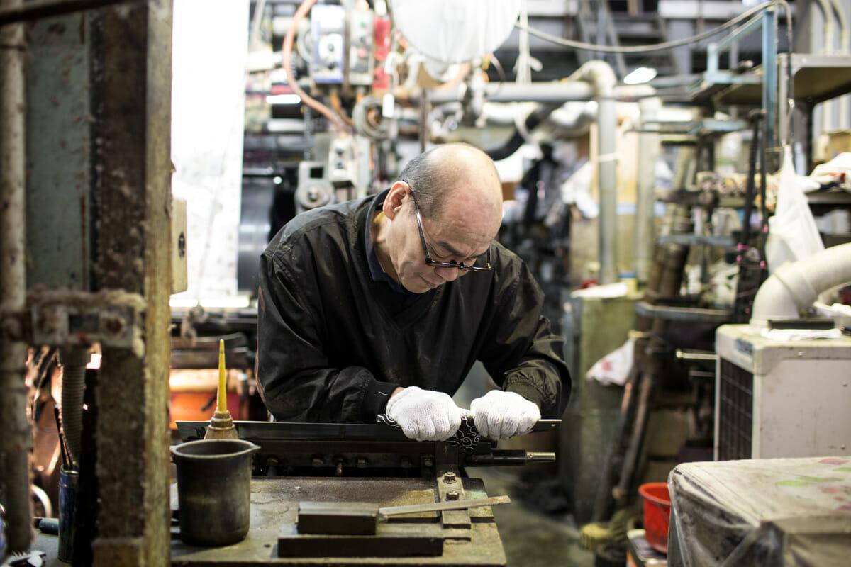 日本で唯一、両面染色技術を持つ職人、角野さん。機械の刃を研いでいるところ