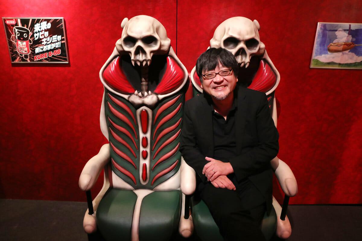 黒い新幹線のシートに腰かける細田監督