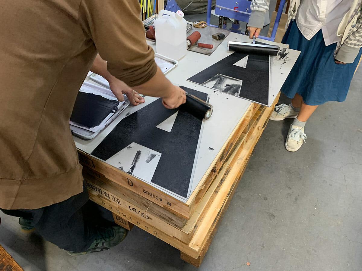 ポスター用につくられた大きな紙活字にインキをのせているところ