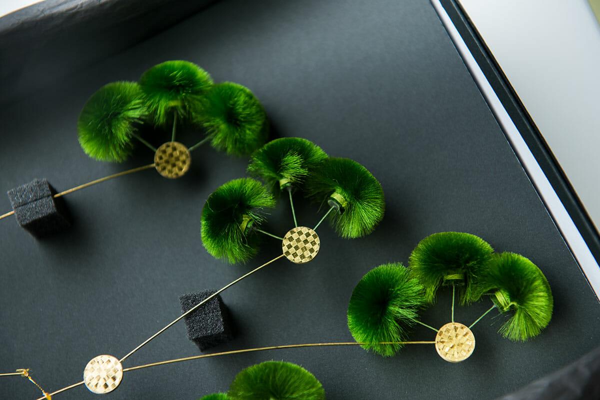本物の松のチクチクしたような葉は、絹糸だけでつくられています。造花とワイヤーを接着する部分は箔押しした紙を使用