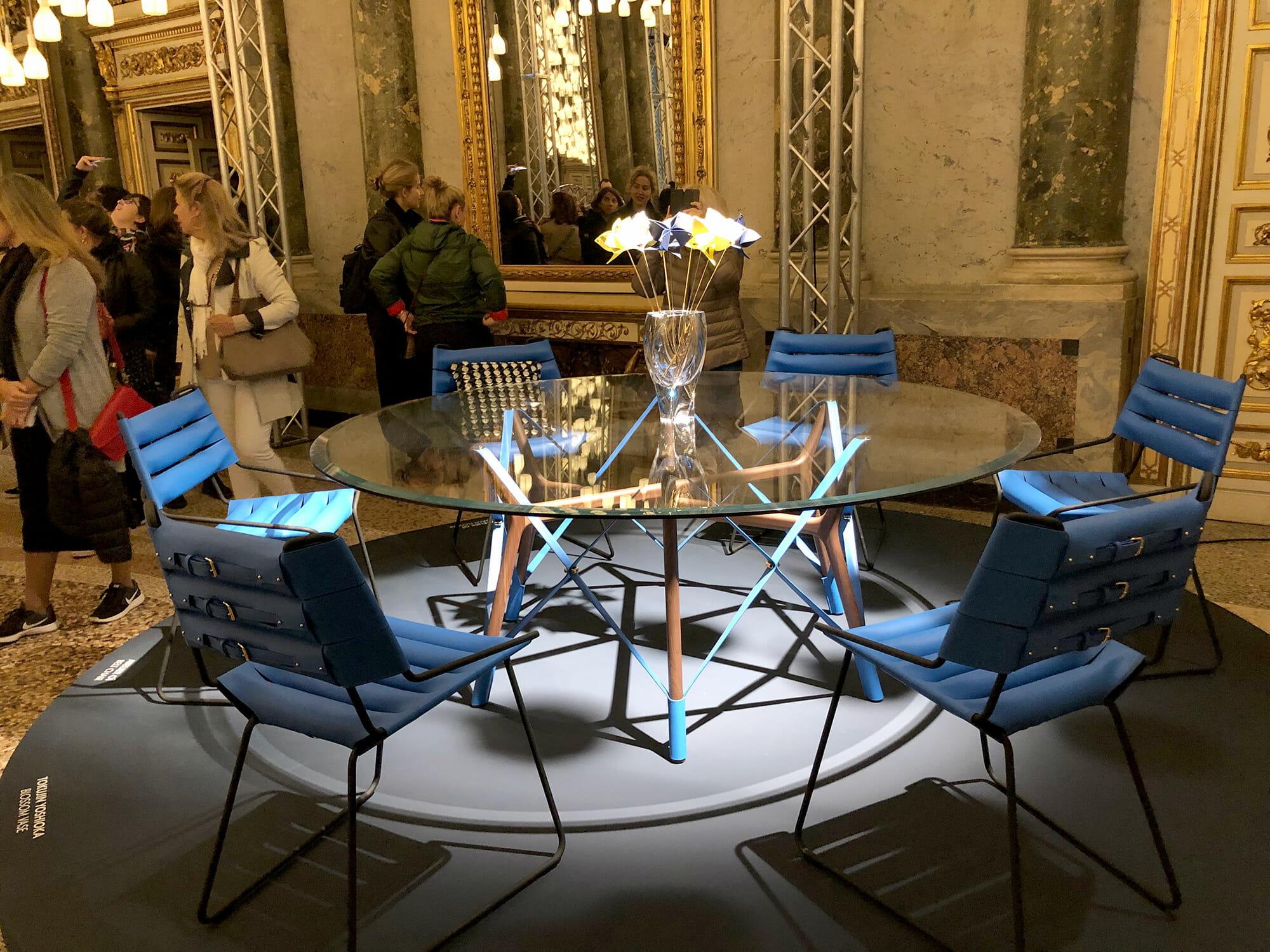 LOUIS VUITTON「オブジェ・ノマド コレクション」、ミラノデザインウィーク定番の展示の一つとなっている、吉岡徳仁さんのフラワーベースとそこに飾られたアトリエ・オイによる花のオブジェ、テーブルと椅子、クッションもアトリエ・オイによるデザイン
