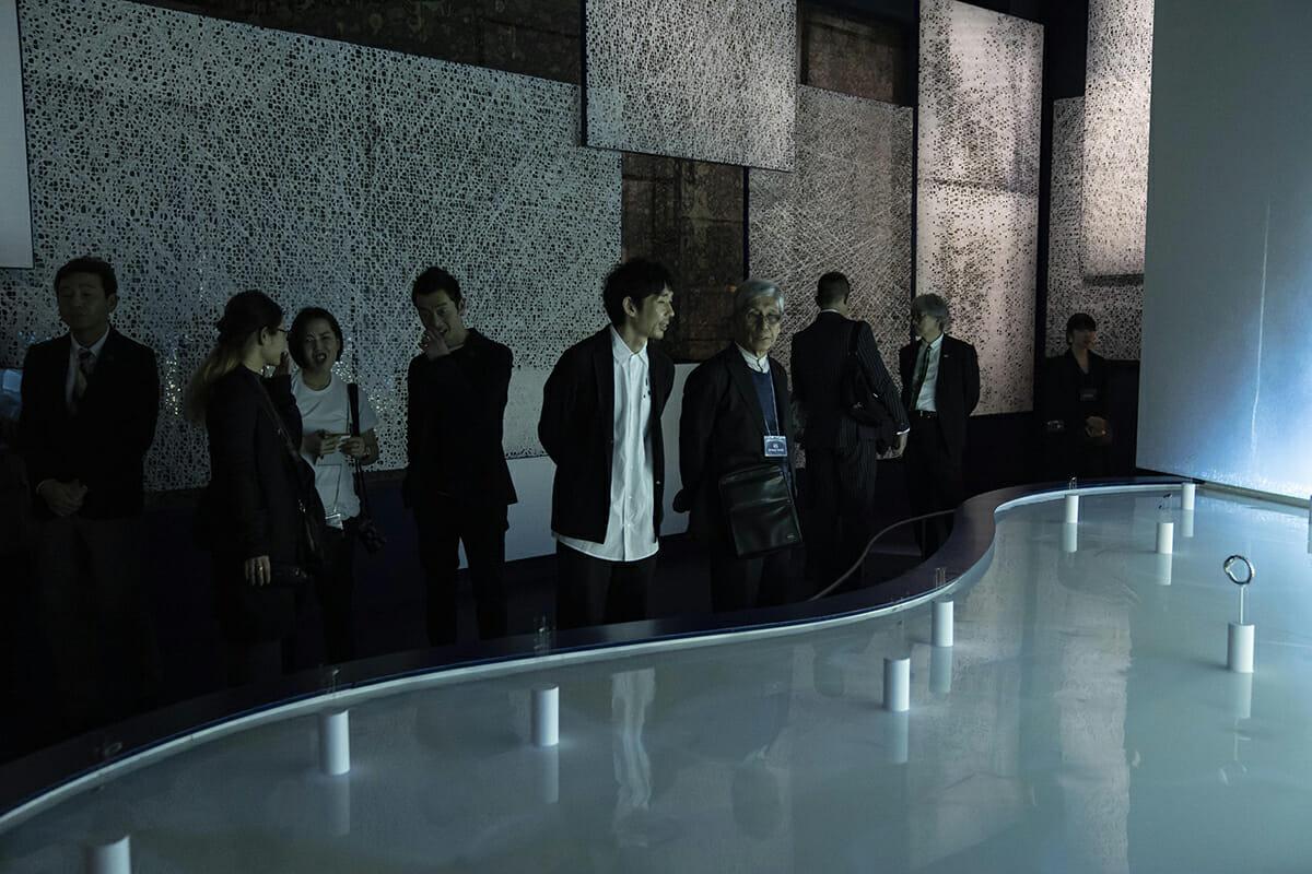 (写真中央)川上元美さんに作品を説明する、we+の安藤北斗さん