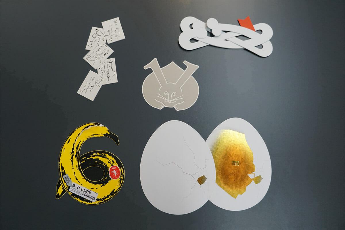 これまでに小玉さんが手がけた年賀状の数々。どれも自由な発想で特殊な印刷技術が用いられている。