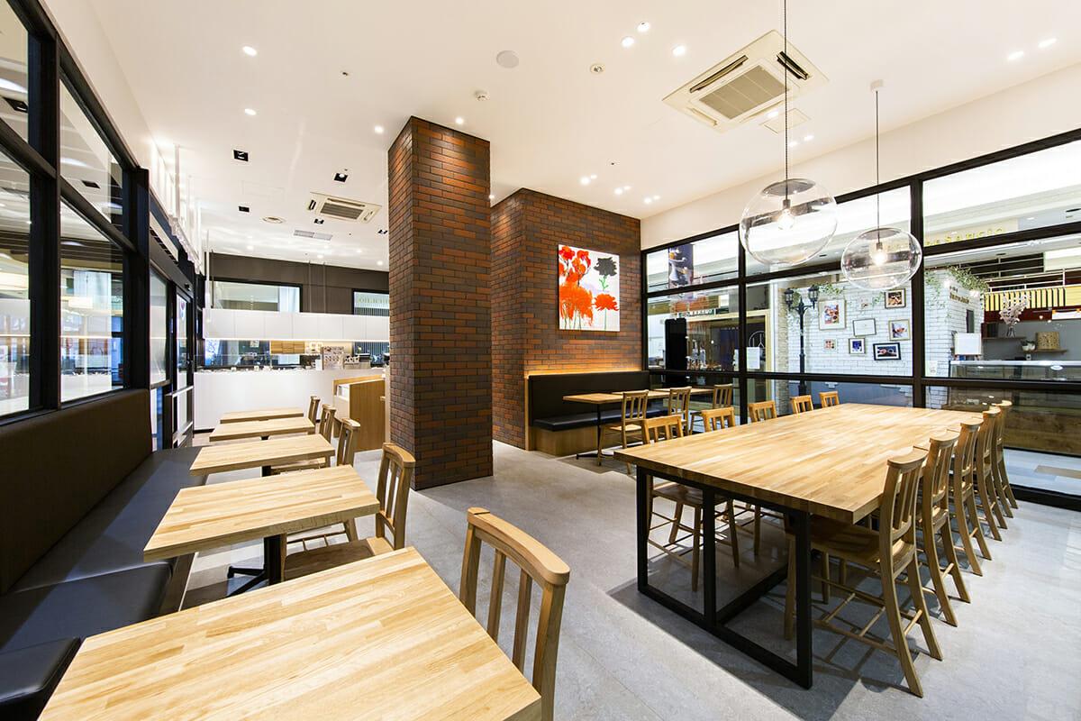 「Soup Stock Tokyo 円山店」レンガで囲まれているゾーンには厨房がある。各店舗の壁には、スマイルズ代表取締役社長である遠山正道さんがつくったタイルアートが設置されている。
