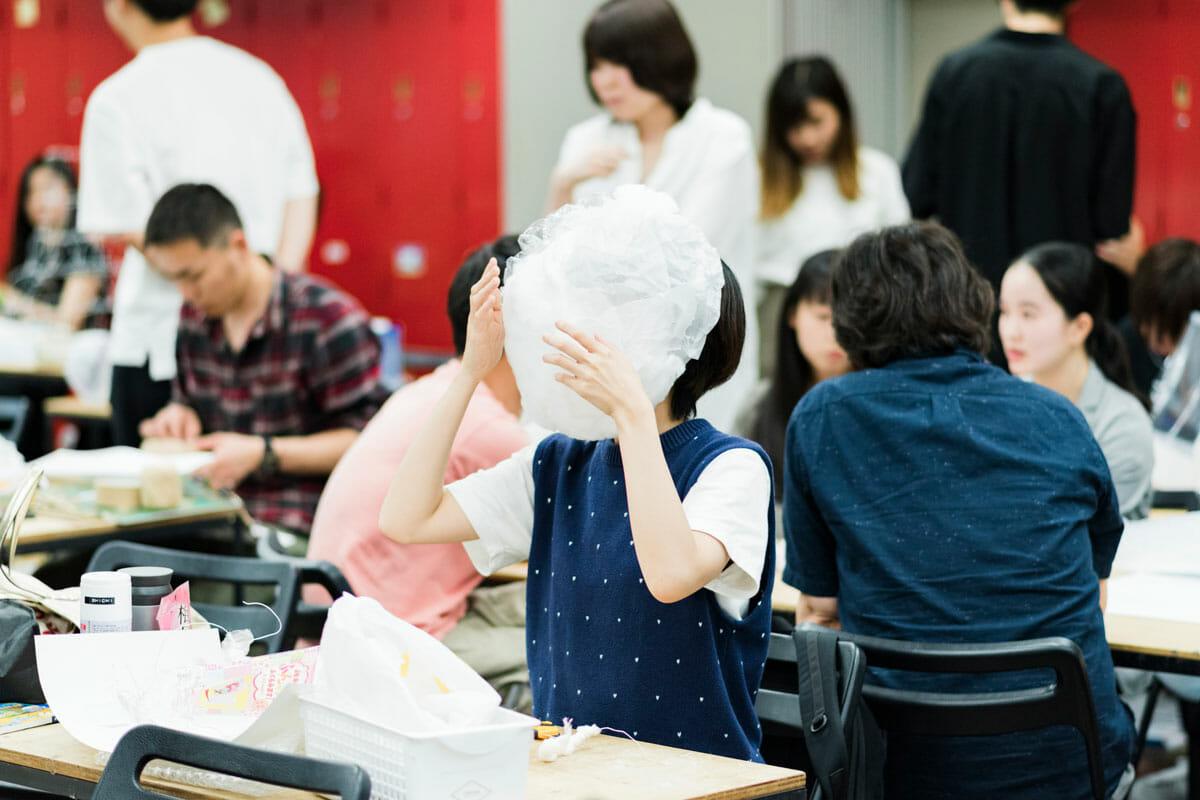 田辺さんが受け持つ1年生の造形課題「ルーツの翻訳」授業風景。 身の回りにあるものを使って頭部、あるいは身体の一部を覆う空間を作成し、自分の精神的なルーツを具体的な空間に翻訳することで、他者にも体験してもらう授業。