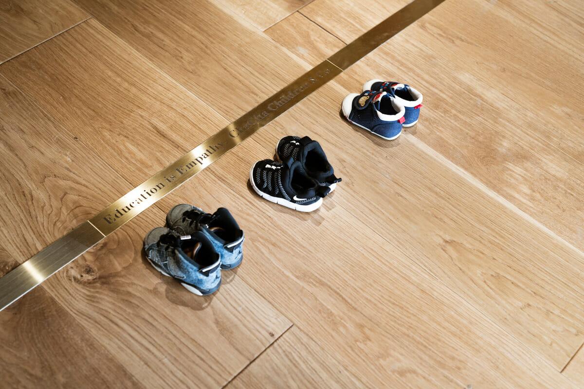 玄関には段差を設けず、靴を脱ぐ場所だと子どもたちがわかるためのヒントとして一本の線が引かれている